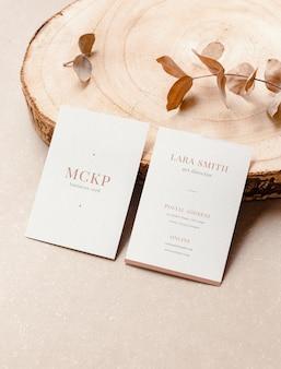 Close up van twee verticale visitekaartjes mockup en organische elementen voor branding presentatie