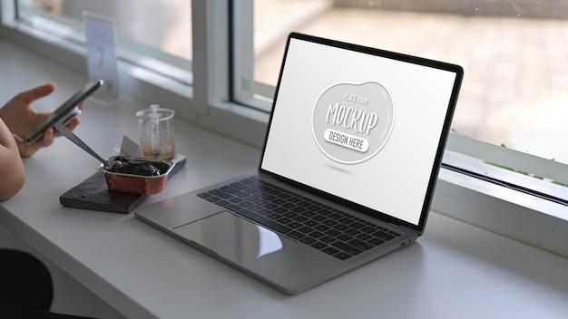 Close-up van vrouw met smartphone met mock up laptopcomputer op witte tafel