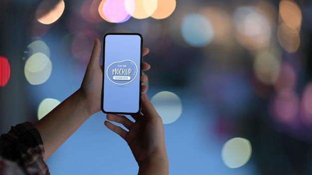 Close-up van vrouwelijke handen met mock-up smartphone op bokeh achtergrond