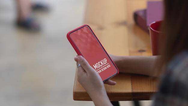 Close-up van vrouwelijke handen met smartphone mockup