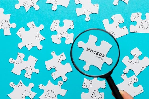 Close-upmens met vergrootglas en stukjes van puzzel