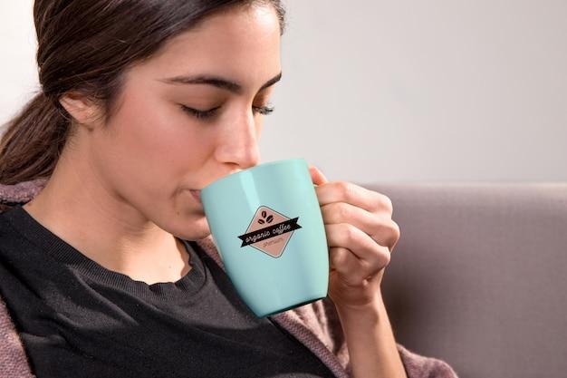 Close-upvrouw het drinken van blauwe mok
