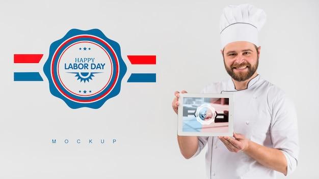 Cocinero sujetando maqueta de tableta para el día de trabajo