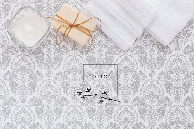 Colocación plana de manteca corporal y jabón en maqueta de fondo liso