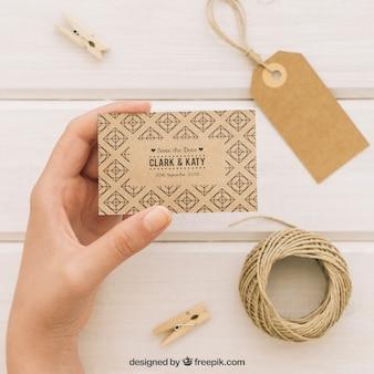Complementos y mano sujetando una plantilla de tarjeta de boda