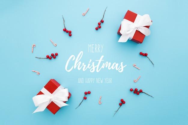 Composición circular con adornos navideños sobre un fondo azul.