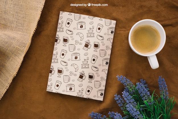 Composición de cubierta de libro con taza de café y flores