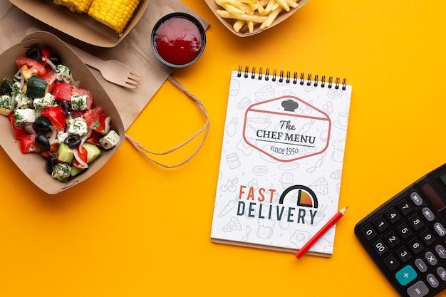 Composición de entrega de alimentos gratis con maqueta de bloc de notas