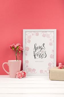 Composición de flores de clavel junto a maqueta de marco