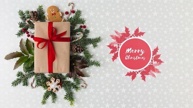Composición navideña con hojas verdes y vista superior de regalo
