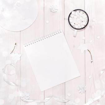 Composición navideña con maqueta de bloc de notas con decoraciones blancas