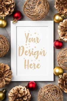 Composición navideña con marco de imagen vacío adorno dorado decoraciones de conos de pino mock up plantilla de tarjeta de felicitación