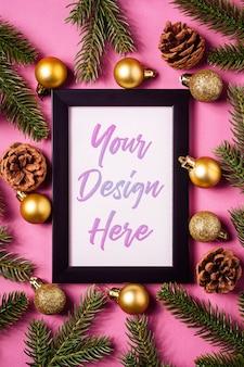 Composición navideña con marco de imagen vacío, bolas navideñas doradas, piñas y ramas de abeto