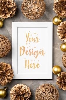 Composición navideña con marco vacío con adornos dorados y piñas