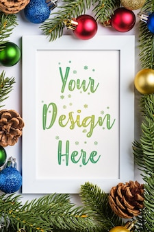 Composición navideña con marco vacío con bolas de colores, piñas y agujas de abeto