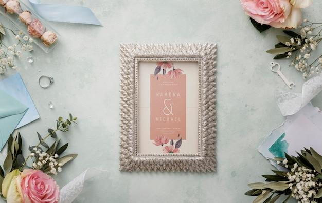 Composición plana de elementos de boda con maqueta de marco