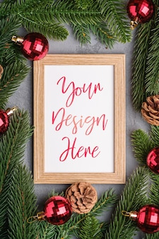 Composición de vacaciones de navidad con maqueta de marco de imagen. adornos rojos y ramas de abeto.