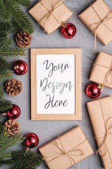 Composición de vacaciones de navidad con maqueta de marco de imagen. adornos rojos, regalos y ramas de abeto.