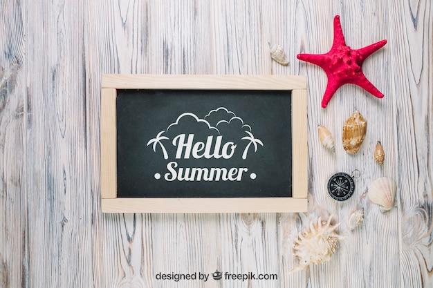 Composición de verano con pizarra y conchas