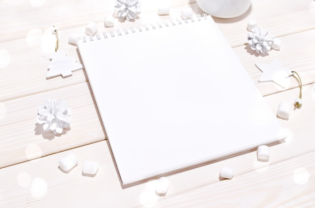 Composizione di natale con mockup di blocco note con decorazioni bianche