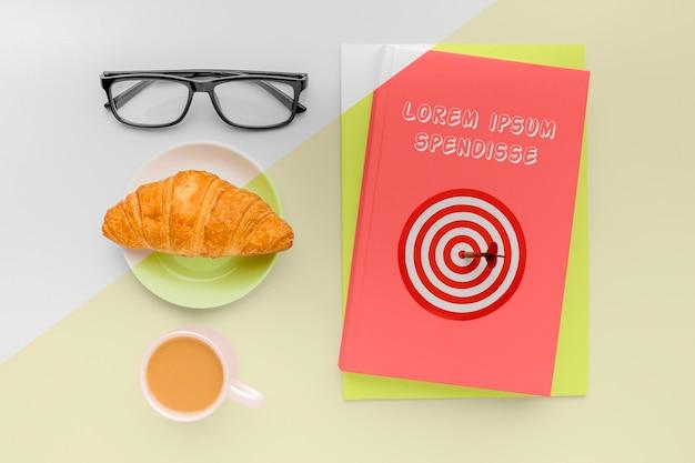 Composizione mock-up di copertina del libro vista dall'alto con una tazza di caffè e cornetto