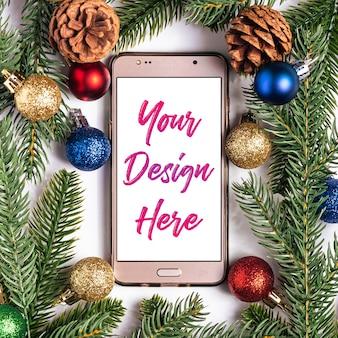 Compras navideñas online. maqueta de smartphone con pantalla en blanco en blanco. bolas de colores, adornos de conos de abeto y pino.