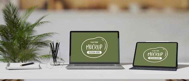 Computadora portátil y tableta digital con pantalla de maqueta en mesa blanca con papelería en 3d render