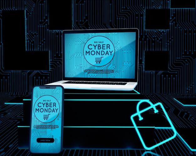 Computadora portátil y teléfono junto al bolso de compras de neón