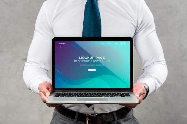 Computer portatile della tenuta dell'uomo del primo piano