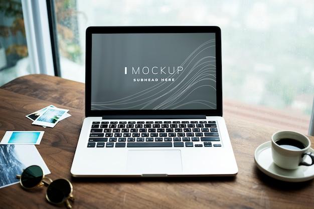 Computer portatile su un tavolo di legno con un mockup di schermo
