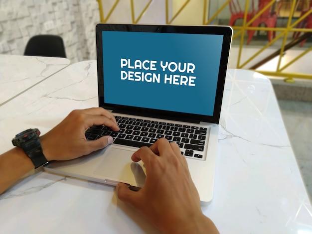 Computer portatile sul tavolo della caffetteria mockup