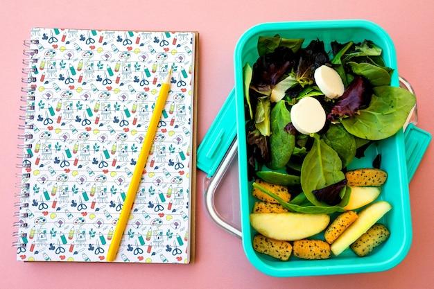 Concepto de comida para llevar con ensalada y libreta