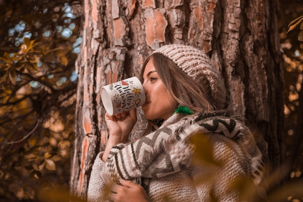 Concepto de otoño con mujer sujetando taza