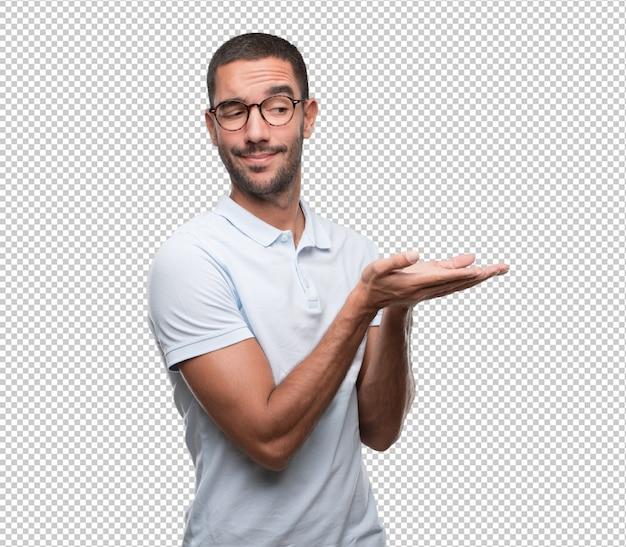 Concepto de un hombre joven feliz sosteniendo algo con su mano