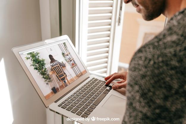 Concepto de oficina en casa con hombre mirando a portátil