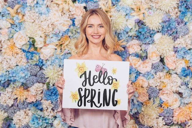 Concepto de primavera con mujer sujetando maqueta de papel