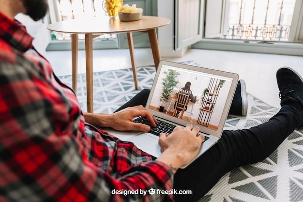Concetto del ministero degli interni con l'uomo sul pavimento facendo uso del computer portatile