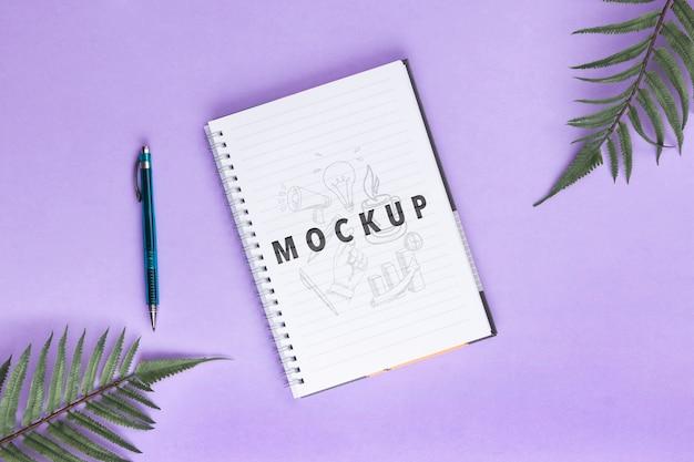 Concetto dello scrittorio con il taccuino e la penna sulla tavola