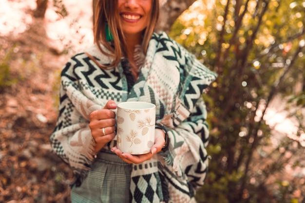 Concetto di autunno con la tazza della holding della donna