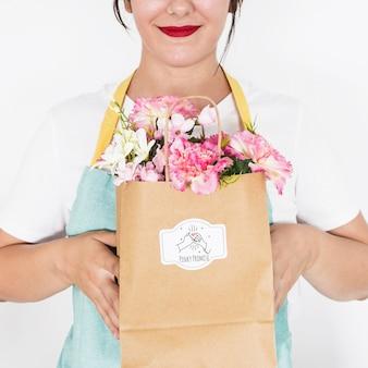 Concetto di giardinaggio con la borsa della tenuta della donna con i fiori