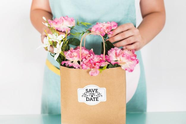 Concetto di giardinaggio con la donna che prepara borsa con i fiori