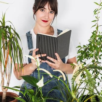 Concetto di giardinaggio con libro di lettura della donna