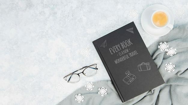 Concetto di libro minimalista con bicchieri e tazza di caffè