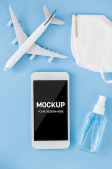 Concetto di pianificazione del viaggio, coronavirus e quarantena. manichino di smartphone con modello di aereo, maschera facciale e spray disinfettante per le mani. vista dall'alto con spazio di copia.
