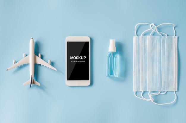 Concetto di pianificazione del viaggio e coronavirus. manichino di smartphone con spray maschera e disinfettante modello di aereo.