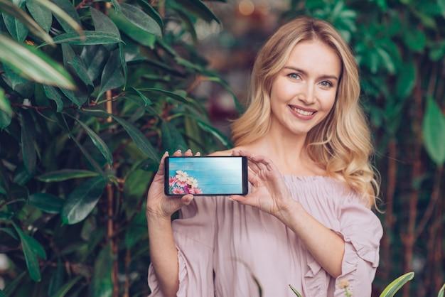 Concetto di primavera con la donna che tiene il modello di smartphone