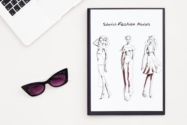 Concetto di scrivania con occhiali da sole e schizzo