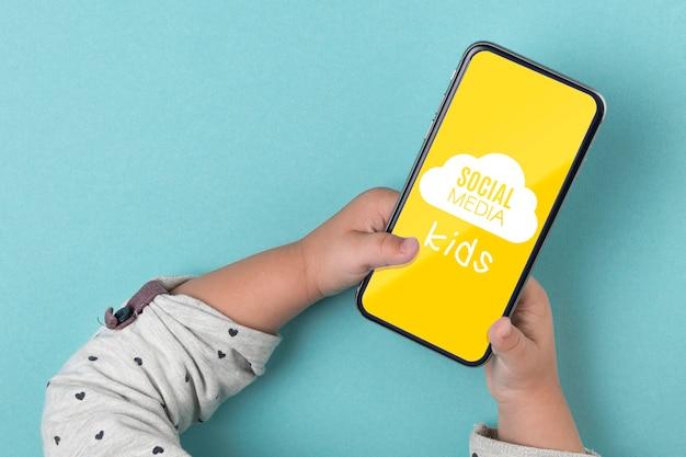 Concetto sociale di media con lo smartphone della tenuta del bambino
