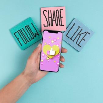 Concetto sociale di media con lo smartphone della tenuta dell'uomo