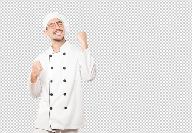 Concurrerende jonge chef-kok die een gebaar van viering maakt